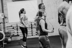 Black and white photo of women and men jumping rope.